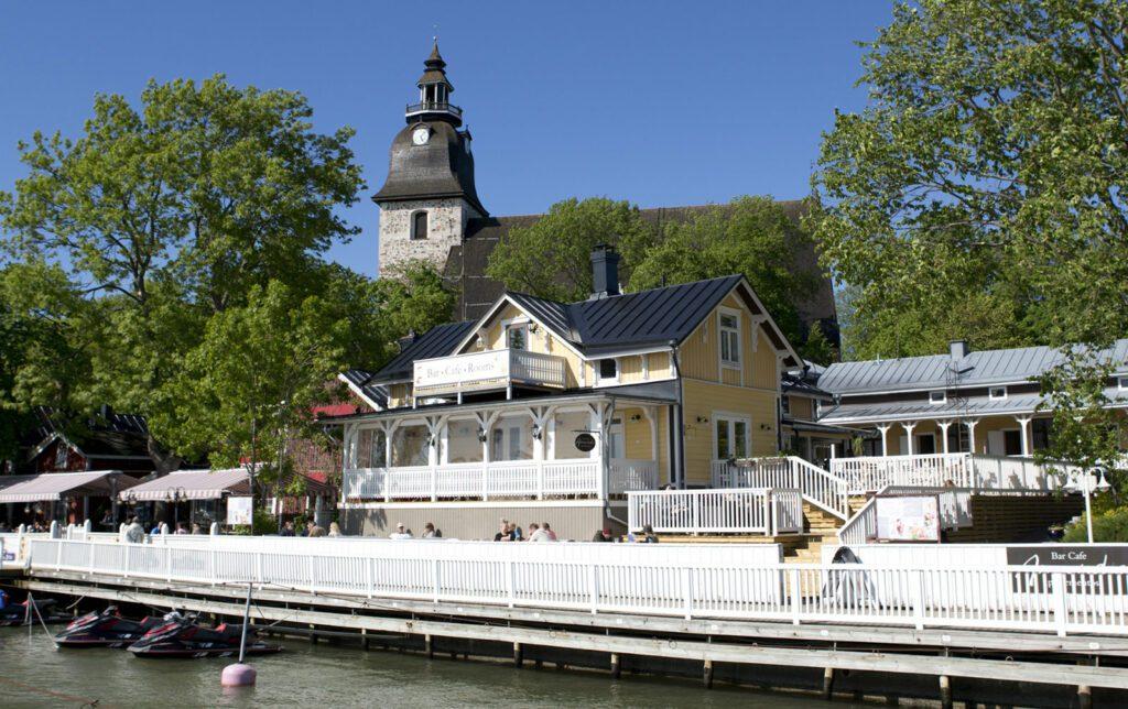 Kahvila Amandiksen rakennus, keltainen päärakennus kuvattu laiturilta päin. Edessä näkyy laiturin valkoinen kaide, rakennuksen sivuilla vihreät korkea puut ja rakennuksen takana Naantalin luostarikirkko, sininen taivas.