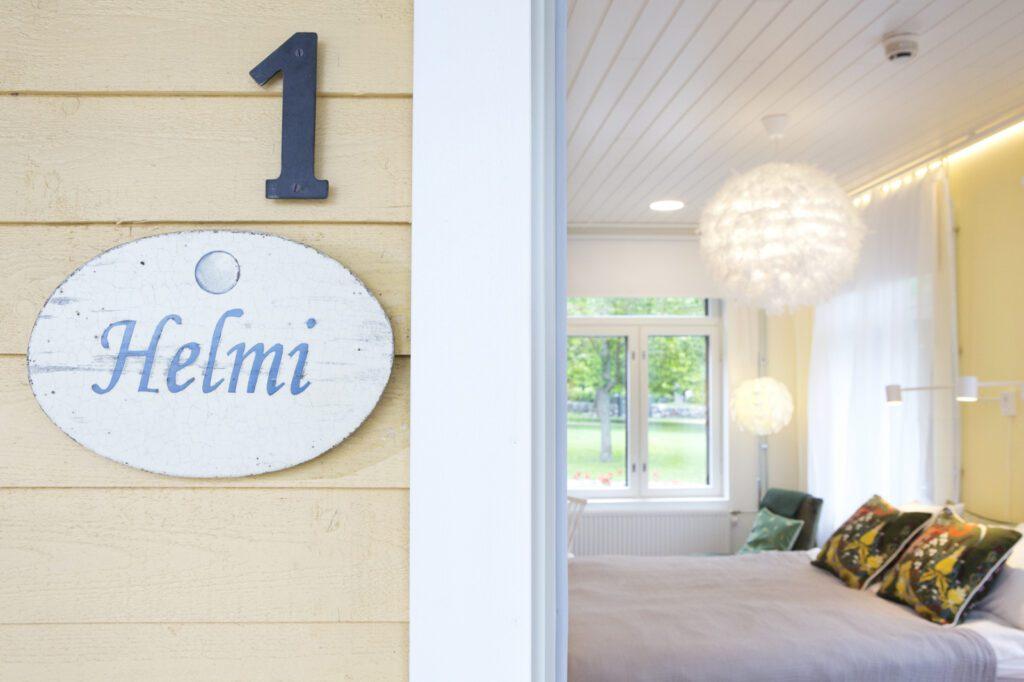 Hotelli Amandiksen huoneen ovenkarmi, jossa lukee Helmi. Oikealla pilkottaa huone, sänky ja ikkuna, josta näkyy puistoa.