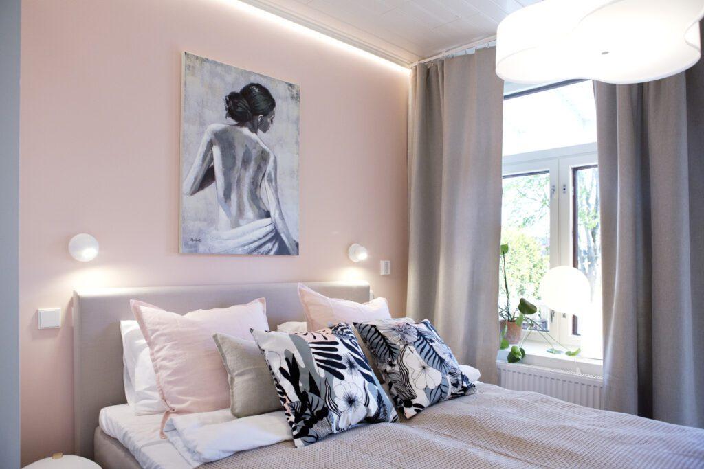 Hotelli Amandiksen huone, jossa vaaleanpunaiset seinät, taulu ja sänky, jossa mustavalkoisia koristetyynyjä.
