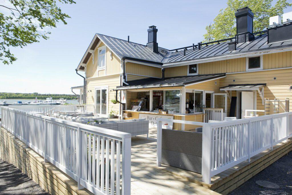 Vaaleankeltainen kahvila Amandis ja terassi, jossa valkoiset kaiteet.