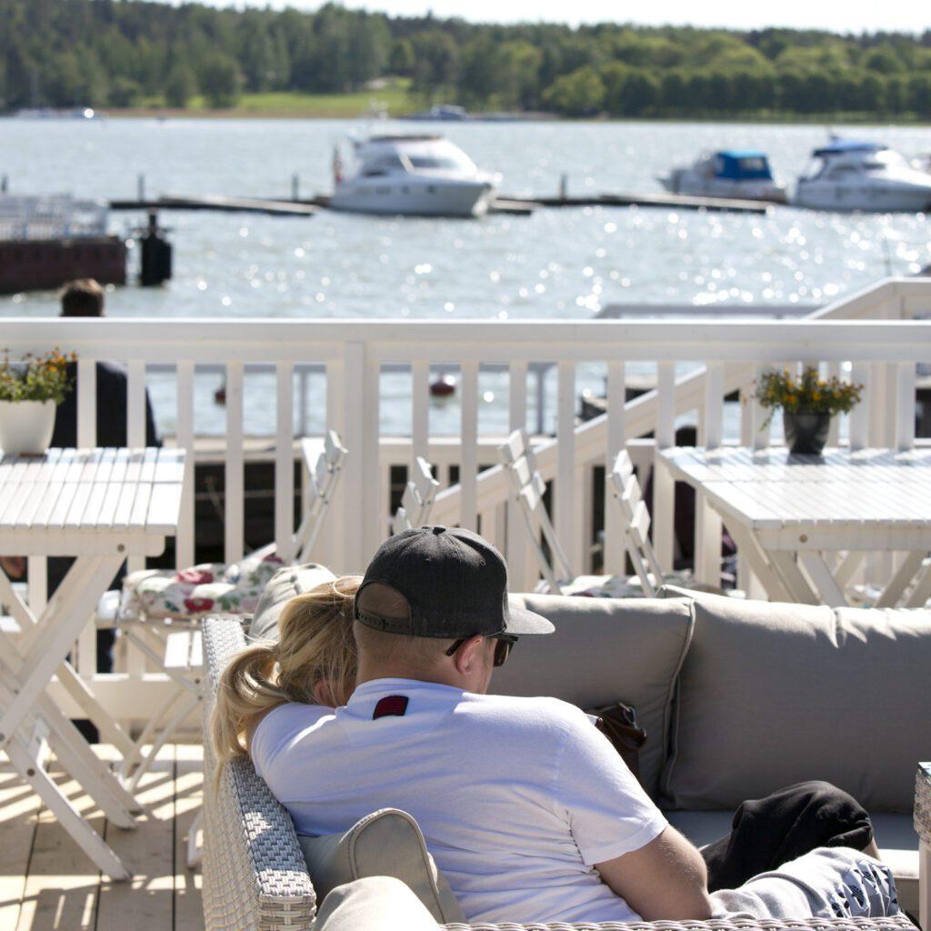 Mies ja nainen istuvat aurinkoisella terassilla. Taustalla meri ja veneitä.
