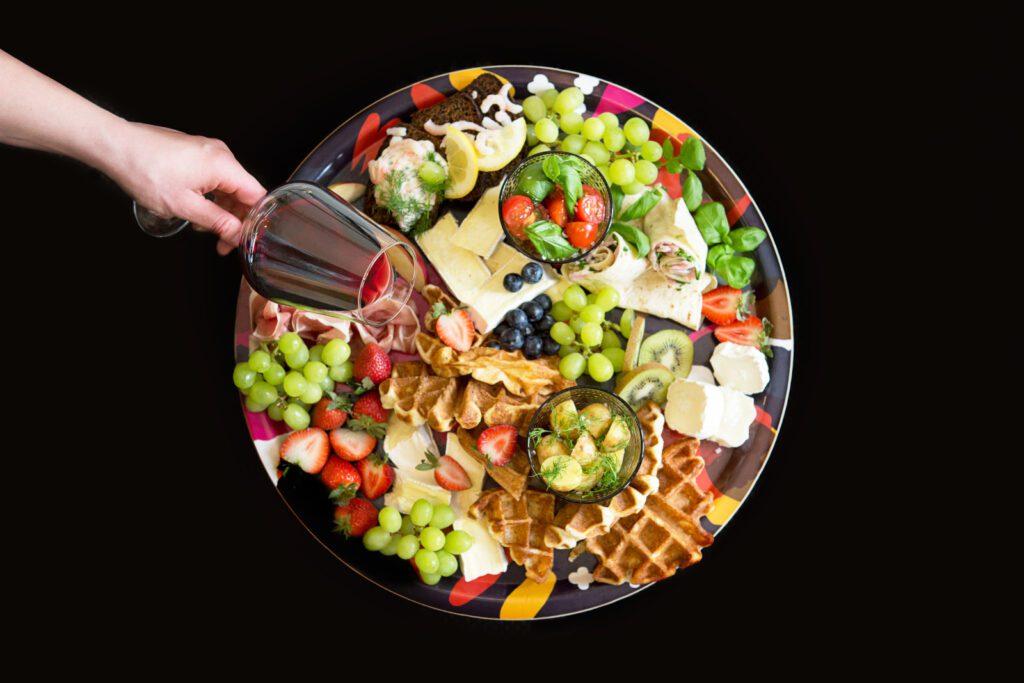 Mustalla taustalla lautanen,, jossa salaattia, viinirypäleitä ja vohveleita.