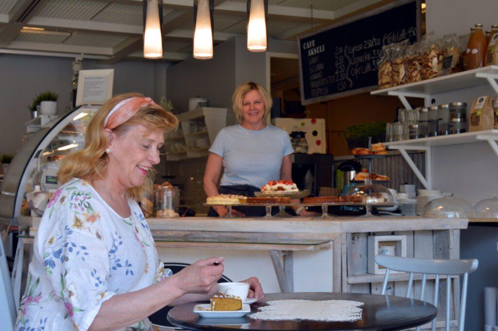 Hymyilevä nainen syö kahvilassa kakkua. Taustalla kahvilan tiski ja hymyilevä tarjoilija kakkulautasten edessä.