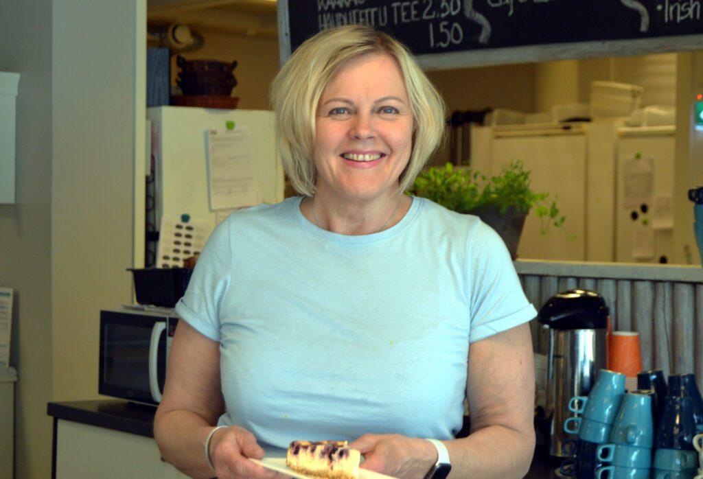 Hymyilevä Cafe Akselin tarjoilija pitää kädessään lautasta, jossa mustikkakakun pala.