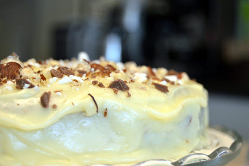 Valkoinen kuorrutettu kakku, jonka päällä suklaata ja pähkinöitä.