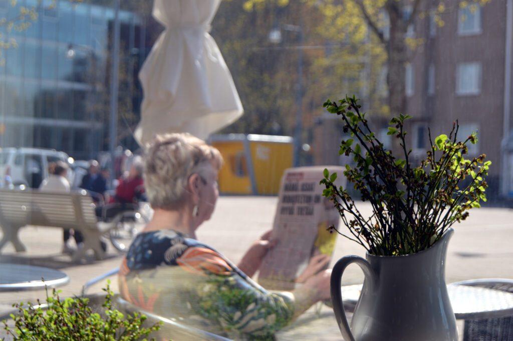 Kahvilan terassilla nainen lukee sanomalehteä.