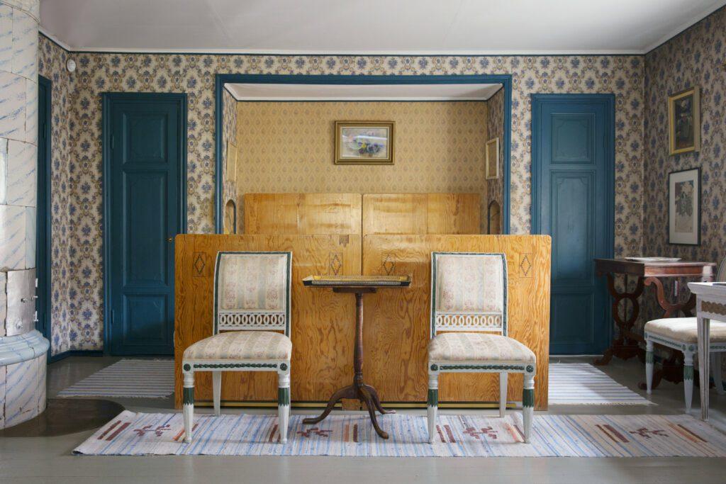 Casa Haartmannin makuuhuone, vaaleanruskea sängynpääty, jota vasten kaksi vaaleaa vanhanaikaista tuolia. Kukkatapettinen seinä ja sinertävät ovet.