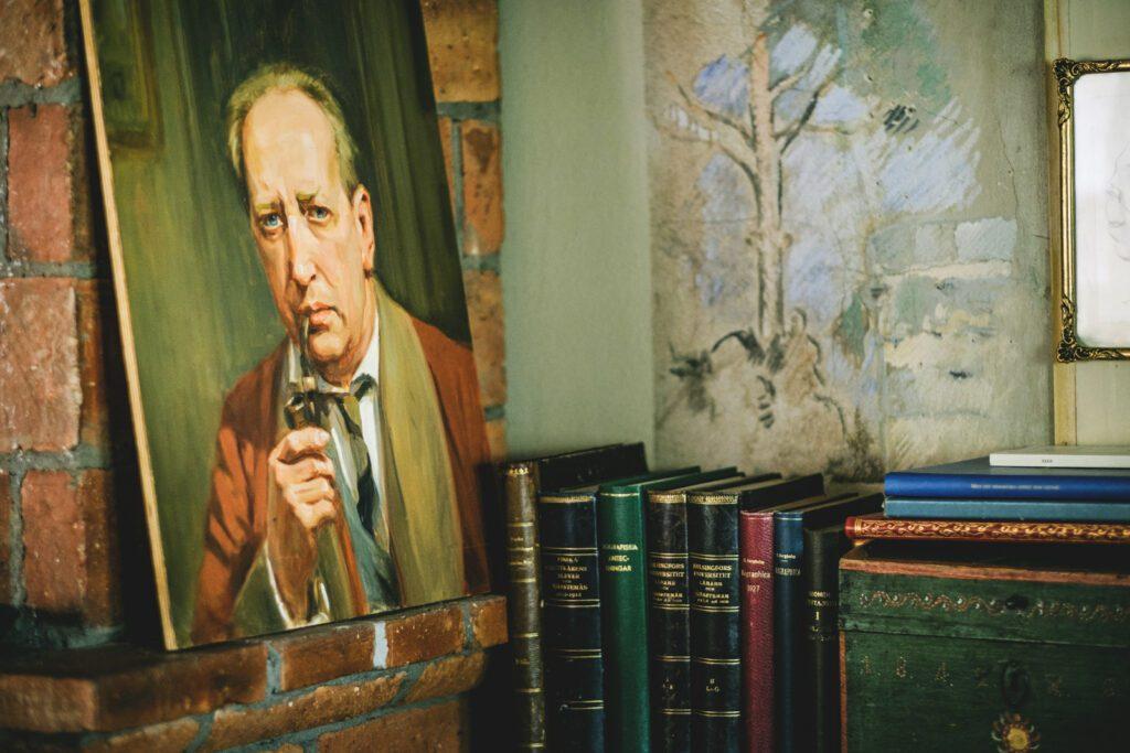 Casa Haartmannin huoneen nurkka, jossa näkyy maalaus miehestä ja rivi monivärisiä kirjoja.