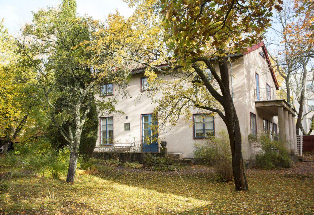 Casa Haartman museo, vaalea päärakennus, puita ja puutarha etualalla, poutainen kesäpäivä.