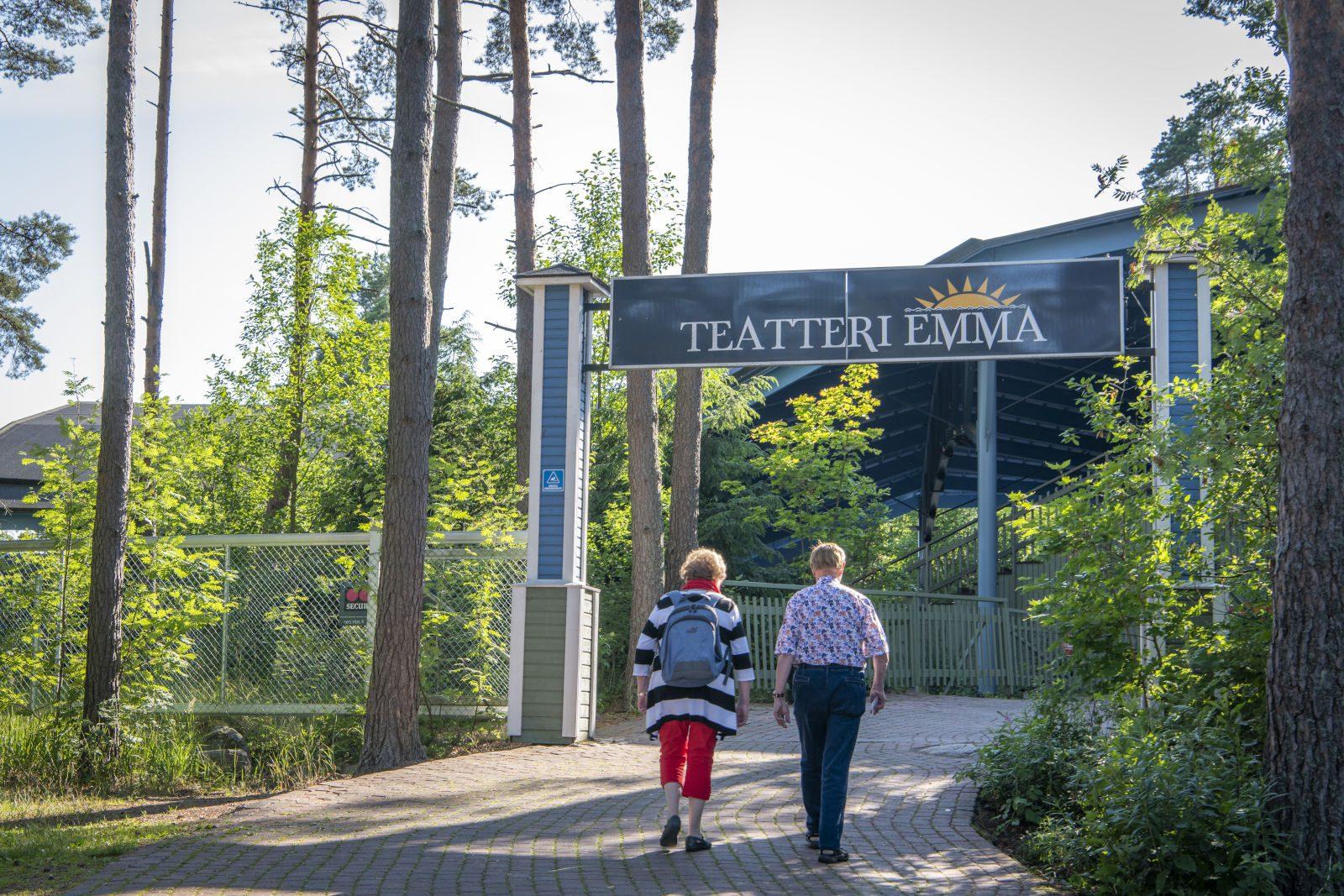 Pariskunta kävelee Emma Teatteria kohden kävelytietä pitkin, metsää ympärillä ja edessä Emma Teatterin kyltti.