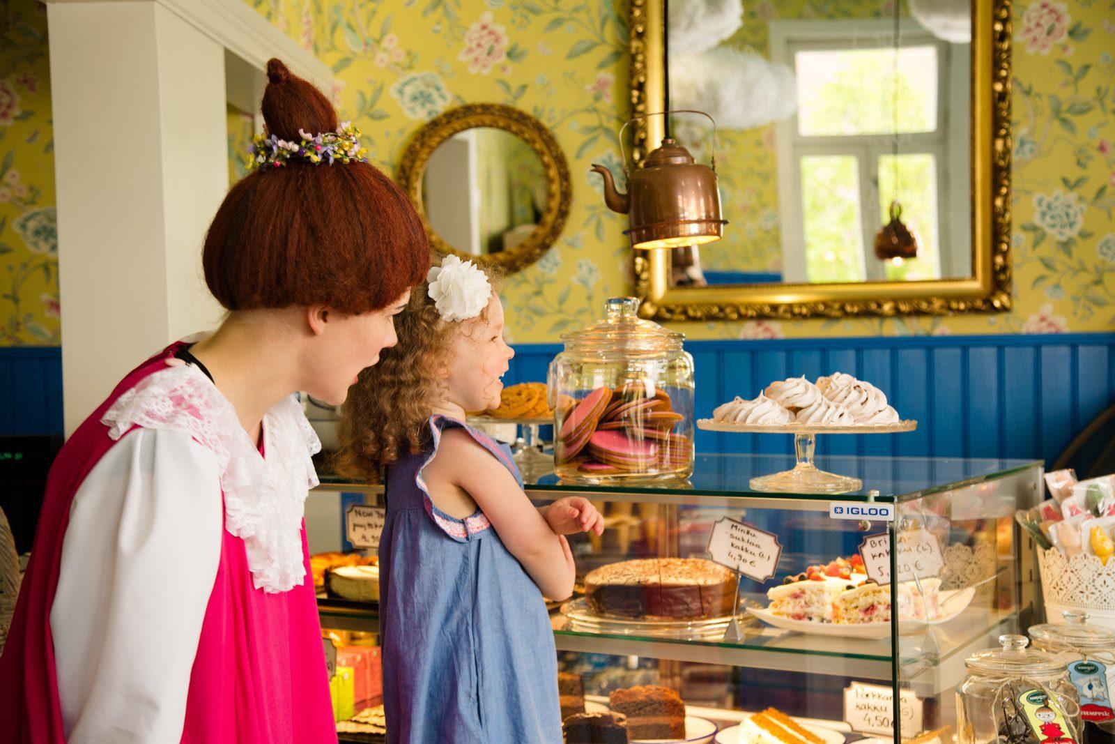 Mymmeli ja pieni tyttö katsovat vitriinin herkkuja kahvilassa, jossa on keltaiset seinät.