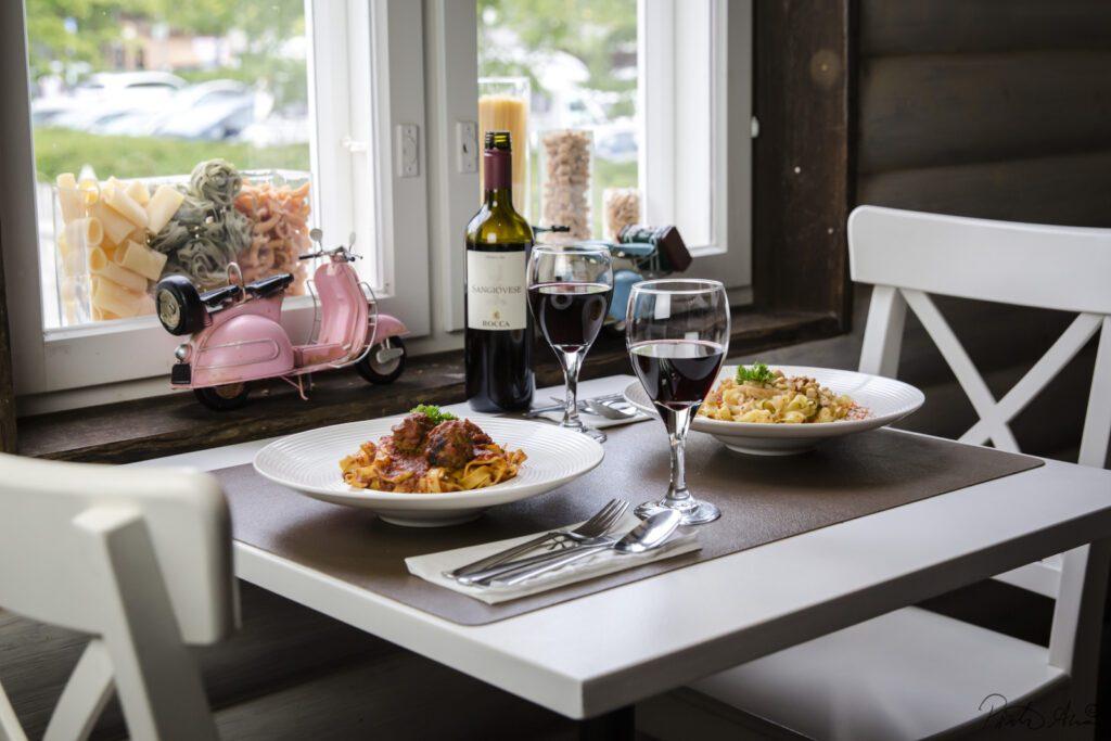 Hasta la pasta -ravintolan kahden henkilön pöytä, jossa kaksi pasta-annosta lautasilla. Lautasten vierssä kaksi lasia punaviiniä, ikkunalaudalla vaaleanpunainen pieni vespa.
