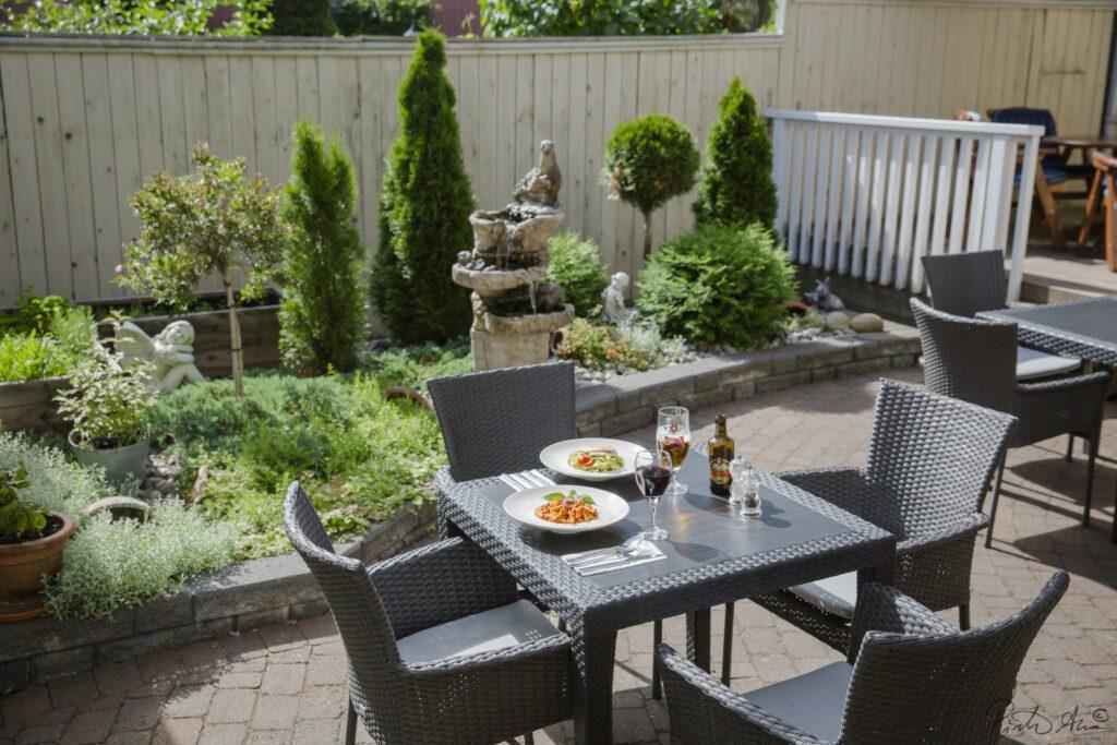 Kahvilan terassi ja puutarha. Harmaan pöytäryhmän päällä kaksi pasta-annosta, viiniä ja olutta laseissa.