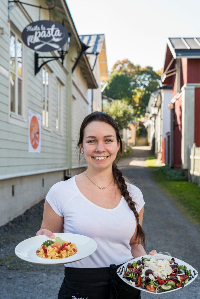 Hymyilevä, valkopaitainen tarjoilijanainen seisoo Naantalin vanhan kaupungin kujalla, Hasta la pasta -ravintolan vieressä, kädessään pasta-annos ja kreikkalainen salaatti lautasilla.