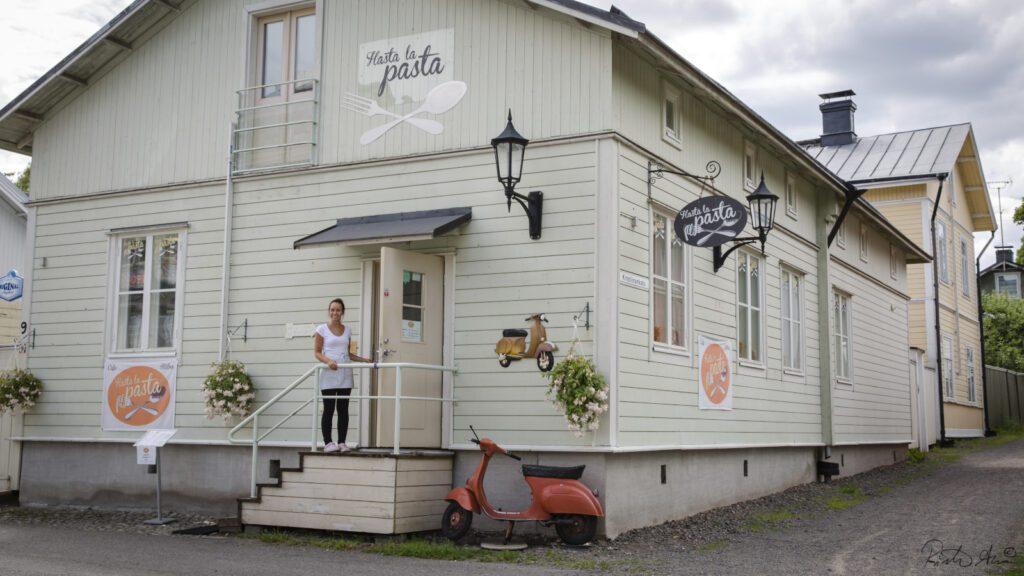 Hasta la pasta -ravintolan julkisivu, vaalean puurakennus, jonka seinässä ravintolan kyltti ja edessä oranssi vespa. Ravintolan portailla seisoo hymyilevä tarjoilijanainen.