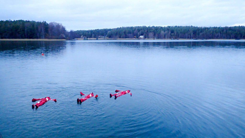 Kolme punaisissa kellunta-asuissa kelluvaa asiakasta meressä Herrankukkaron edustalla.