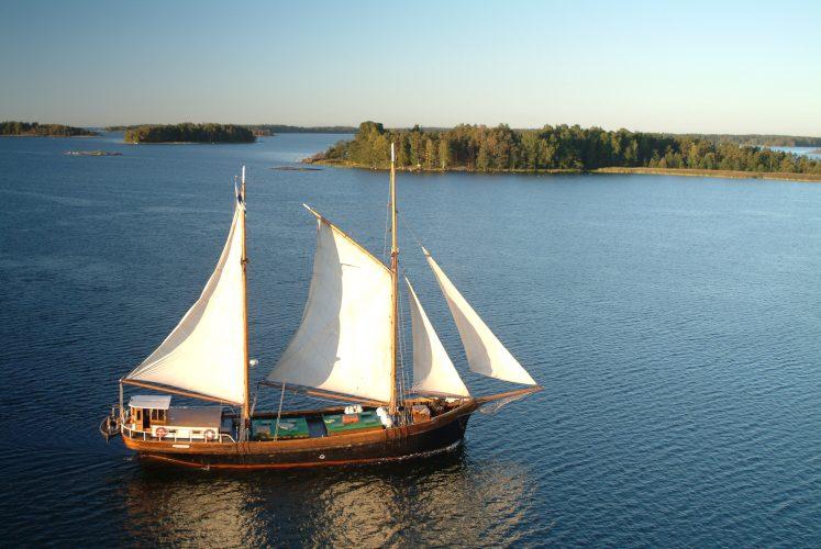 Perinnepurjelaiva Inga-Lill purjehtii merellä, horisontissa saaria ja pilvetön taivas.