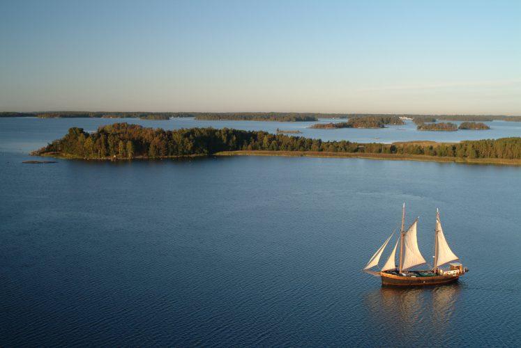 Merimaisema, merta, saaria ja pilvetön taivas. Ulapalla purjehtii perinnepurjelaiva Inga-Lill, valkoiset purjeet.
