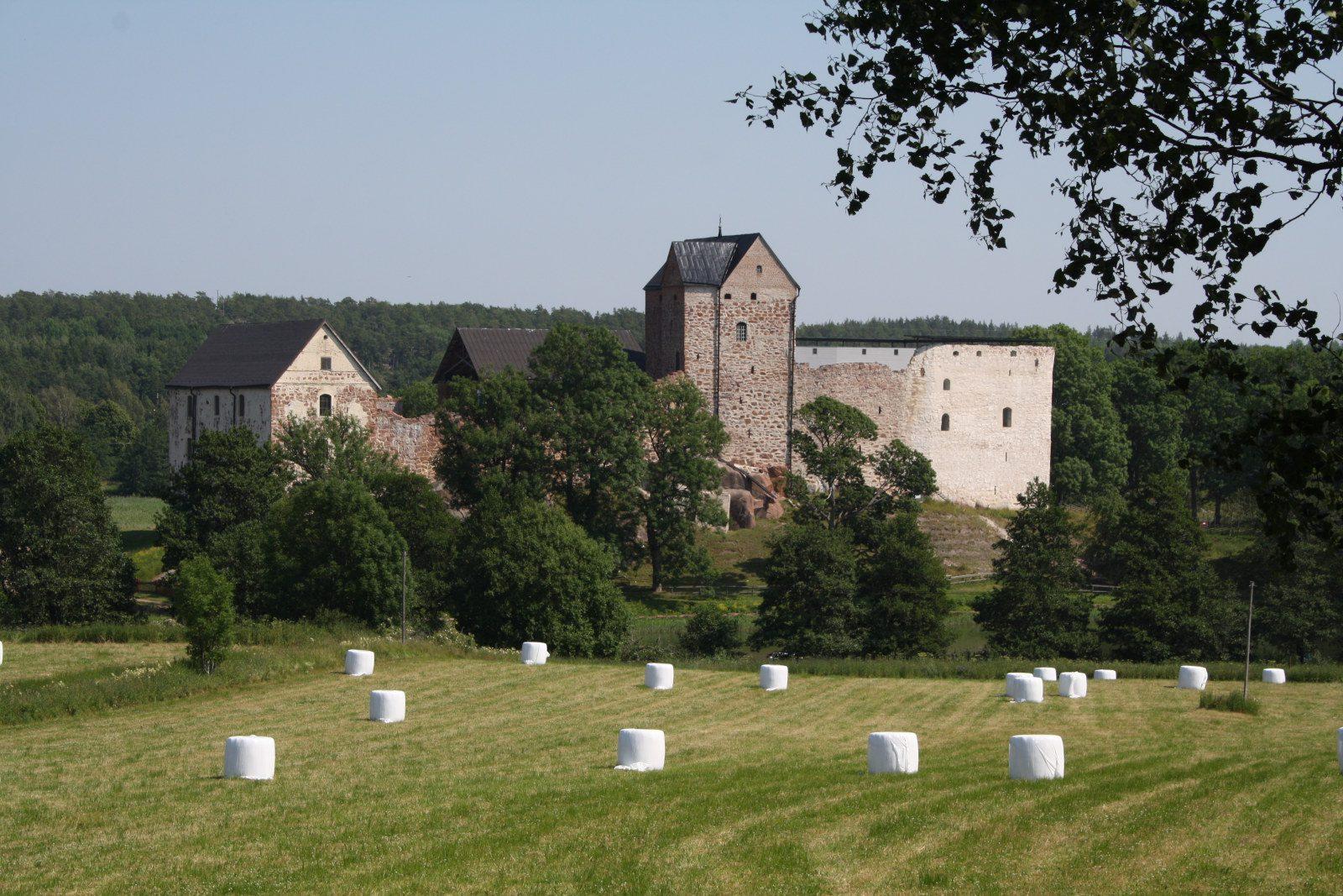 Kastelholman linnan rakennukset Ahvenanmaalla, edustalla peltoa ja valkoisia heinäpaaleja.