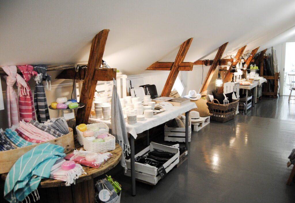 Tarja Ritari Designin ullakkoshopin hyllyjä ja pöytiä, jossa pyyhkeitä sekä astioita.