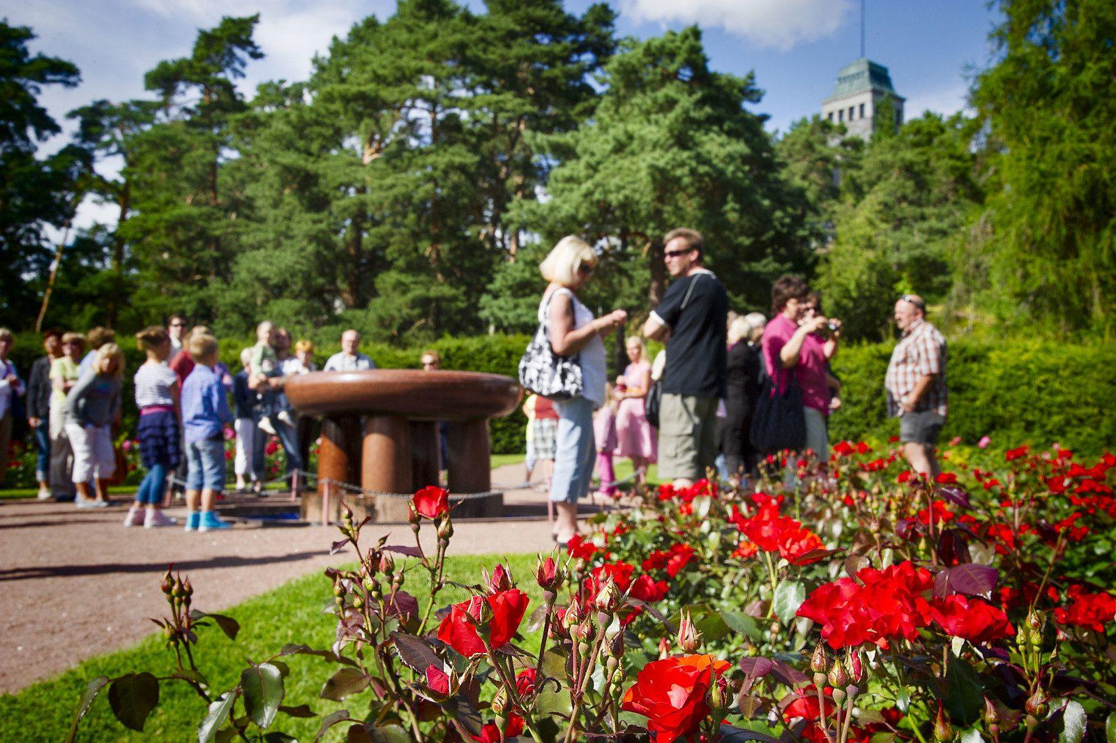Punaisia kukkia Kultarannan puutarhassa, taustalla ihmisiä suihkulähteen ympärillä. Puita ja Kultarannan kivilinnan torni näkyvät takana.
