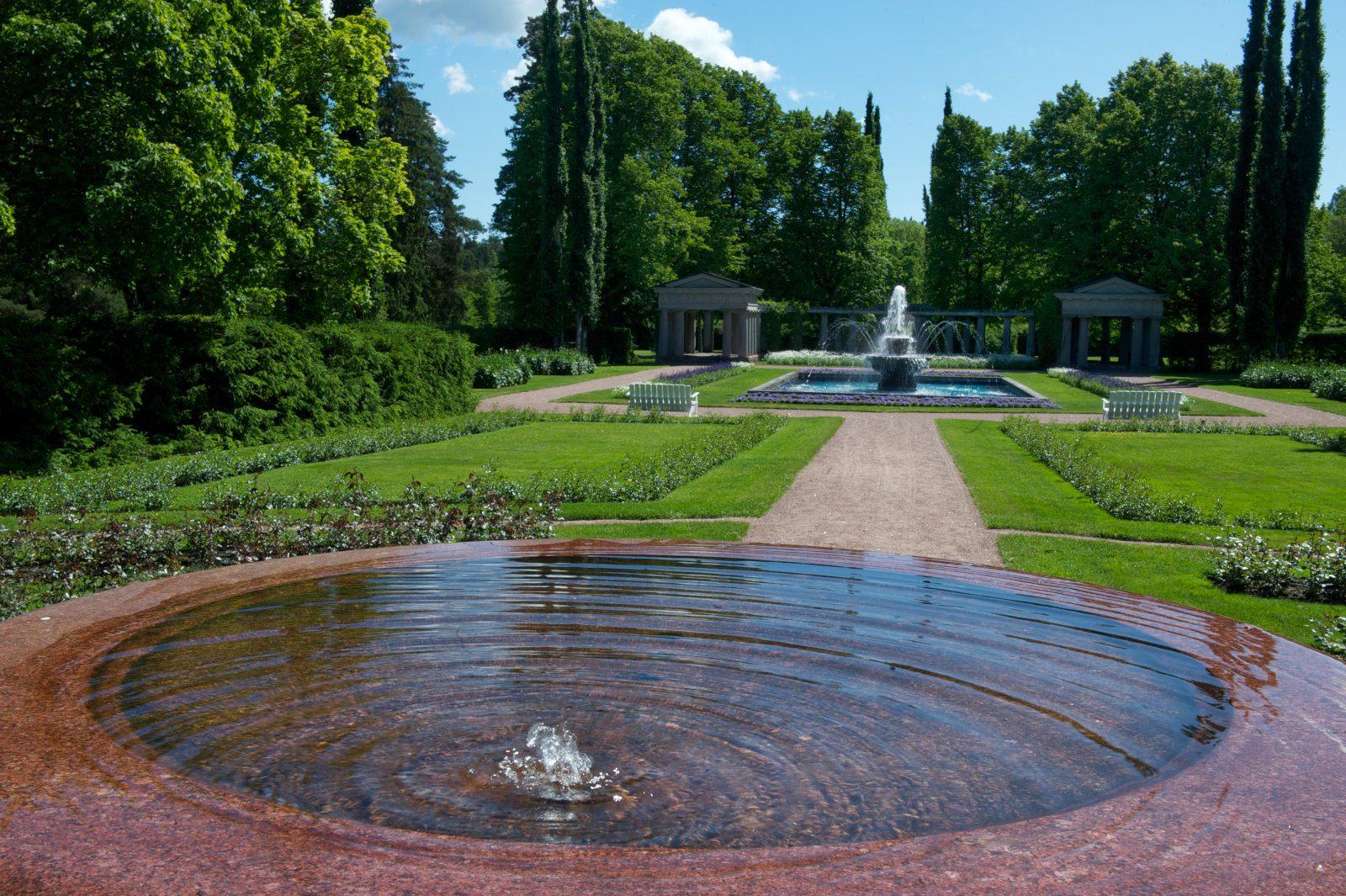 Kultarannan puutarhan graniittinen suihkulähde, jossa pulppuaa vesi.