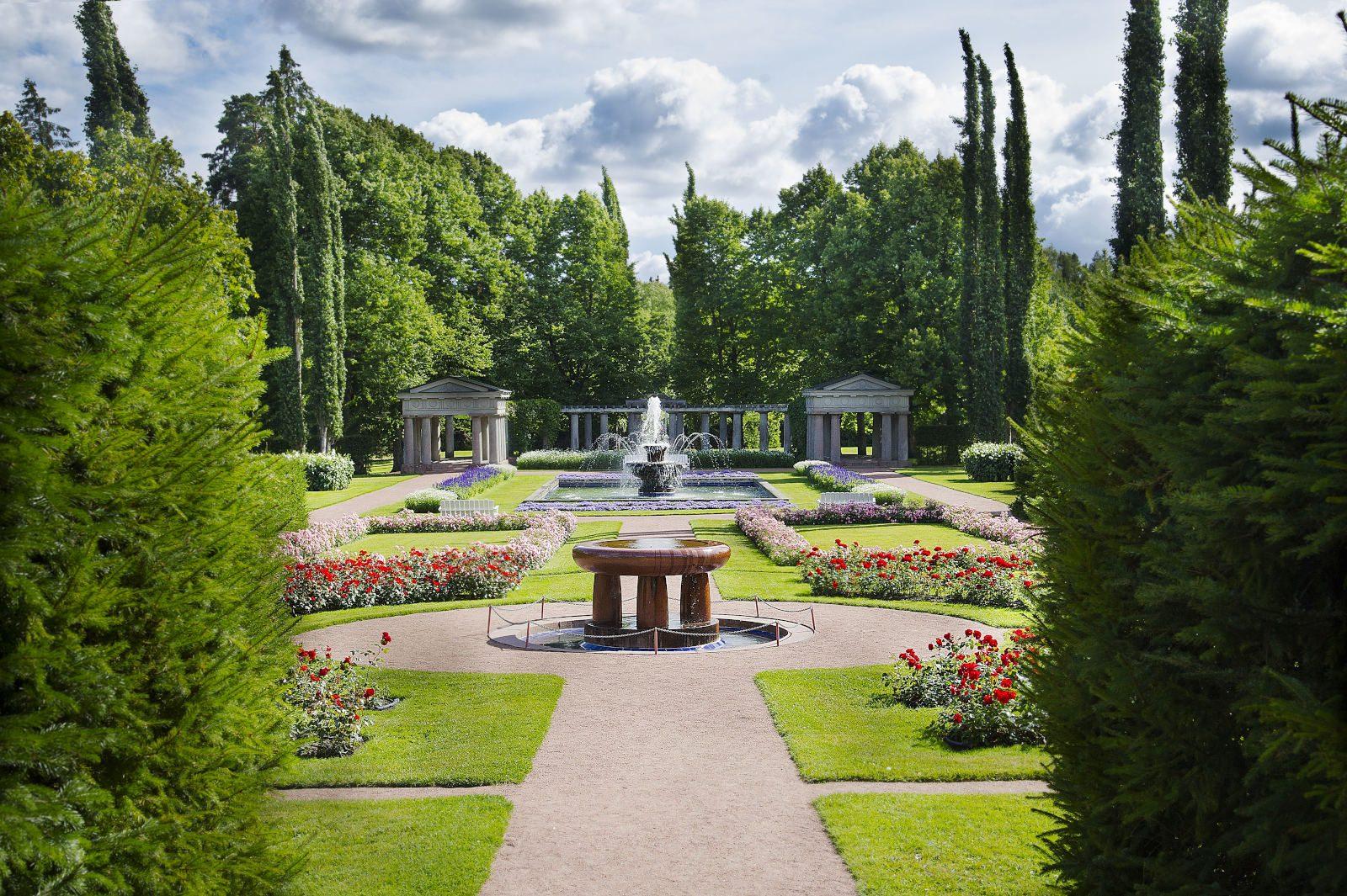 Kultarannan muotopuutarhan keskikäytävä, kaksi suihkulähdettä ja iso paviljonki taustalla. Kuvaa reunastaa kuusiaidat ja kukkaistutukset. Taivas on pilivinen.