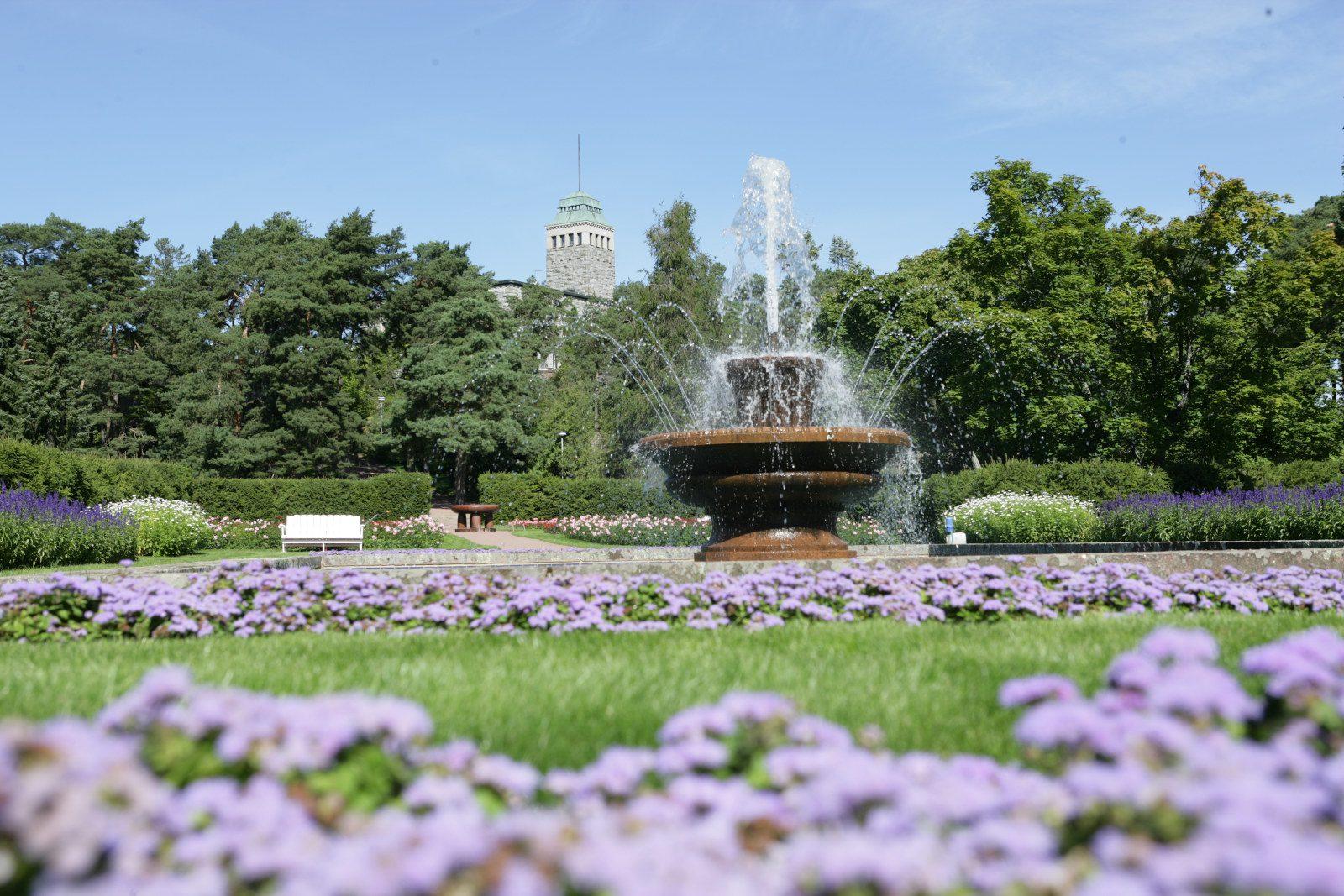 Kultrannan puutarhan iso suihkulähde, violetteja kukkia ja Kultarannan kivilinna.
