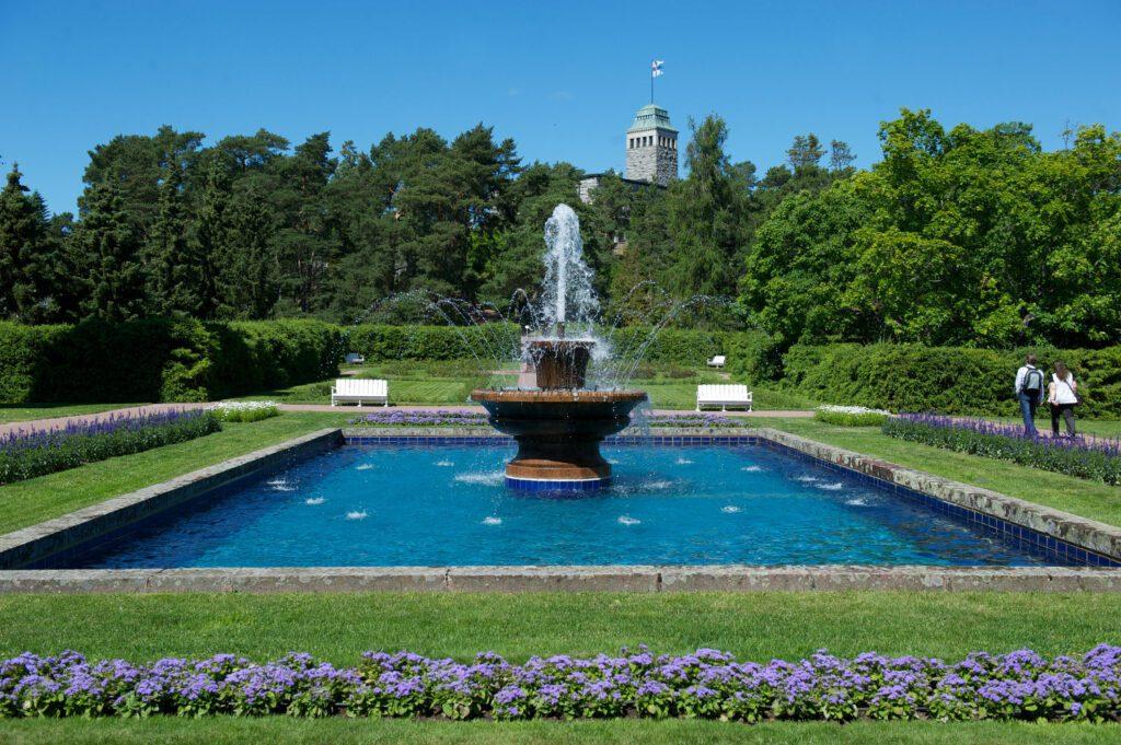 Suihkulähde ja sininen allas. Ympärillä Kultarannan puutarha ja kaksi matkailijaa. Taustalla Kultarannan kivilinna, jonka tornissa liehuu Suomen lippu.