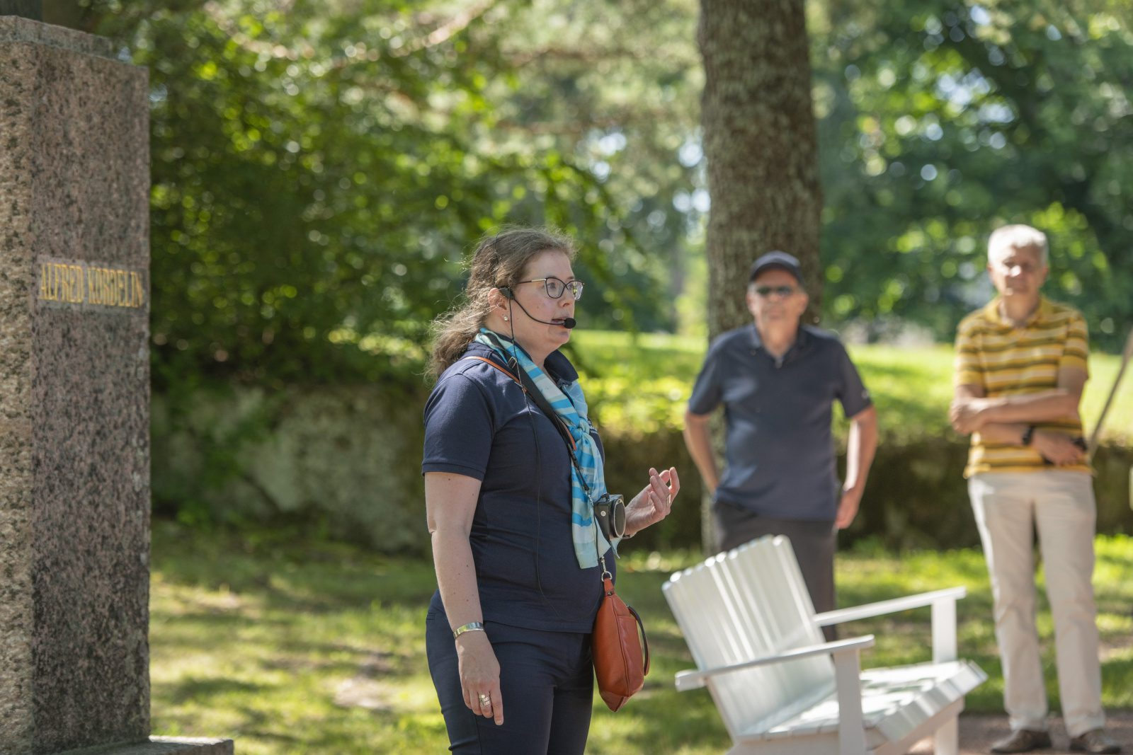 Opas-nainen seisoo Alfred Kordelinin patsaan edessä ja puhuu mikrofoniin. Taustalla kaksi miestä.