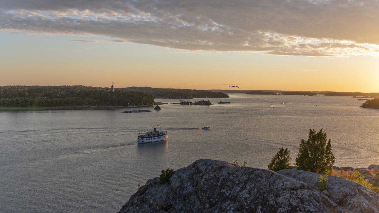 Naantalinlahti Kuparivuoren kallioilta auringonlaskun aikaan, lahdella ajaa valkoinen Rudolfina-laiva Kultarannan kivilinnan edusatlla.