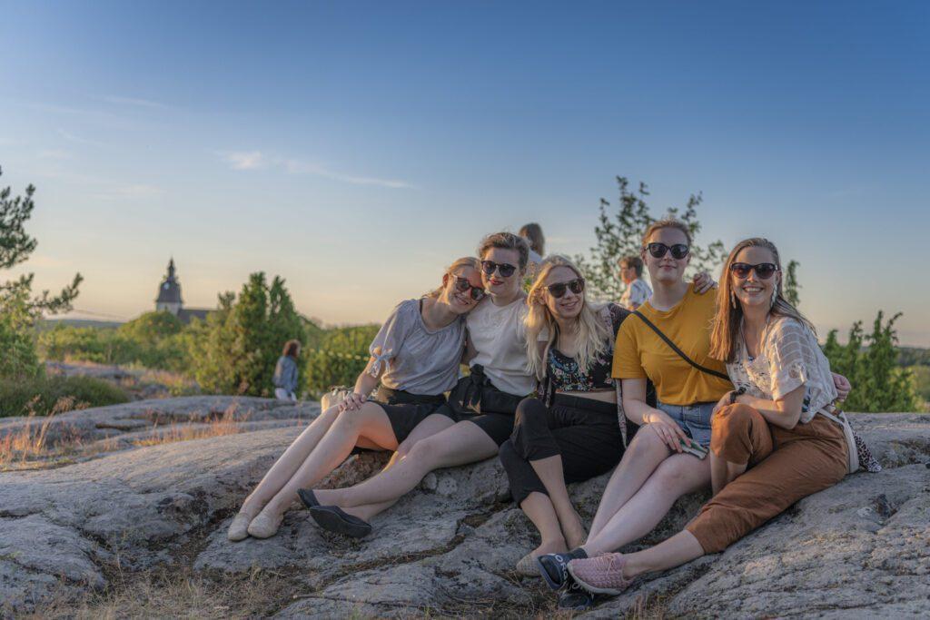 Viisi aurinkolasipäistä tyttöä istuu Kuparivuoren kallioilla kesällä, taustalla Naantalin kirkon siluetti.