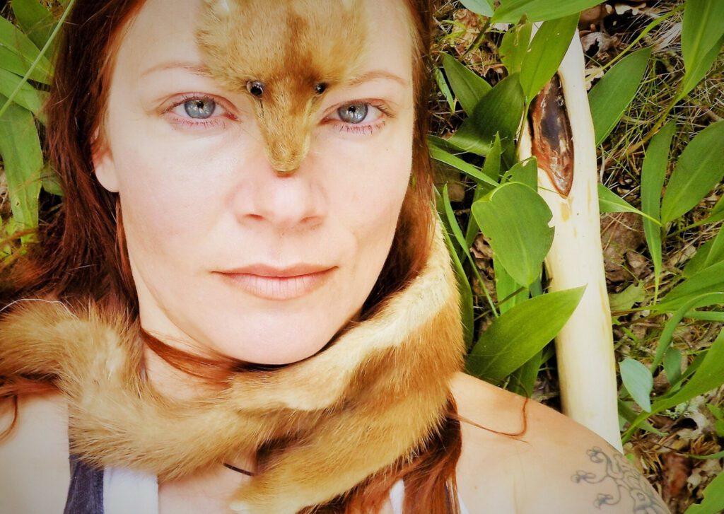 Kuppari-Hanna katsoo kameraan metsäluonnossa ja kärpännahka päällään.