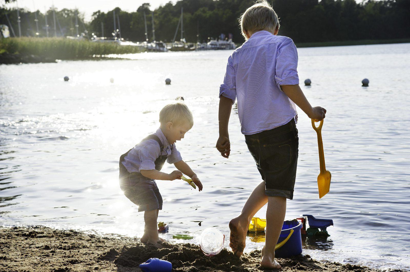 Kaksi lasta rannalla, leikkivät vesirajassa. Toisella on kädessä keltainen lapio.