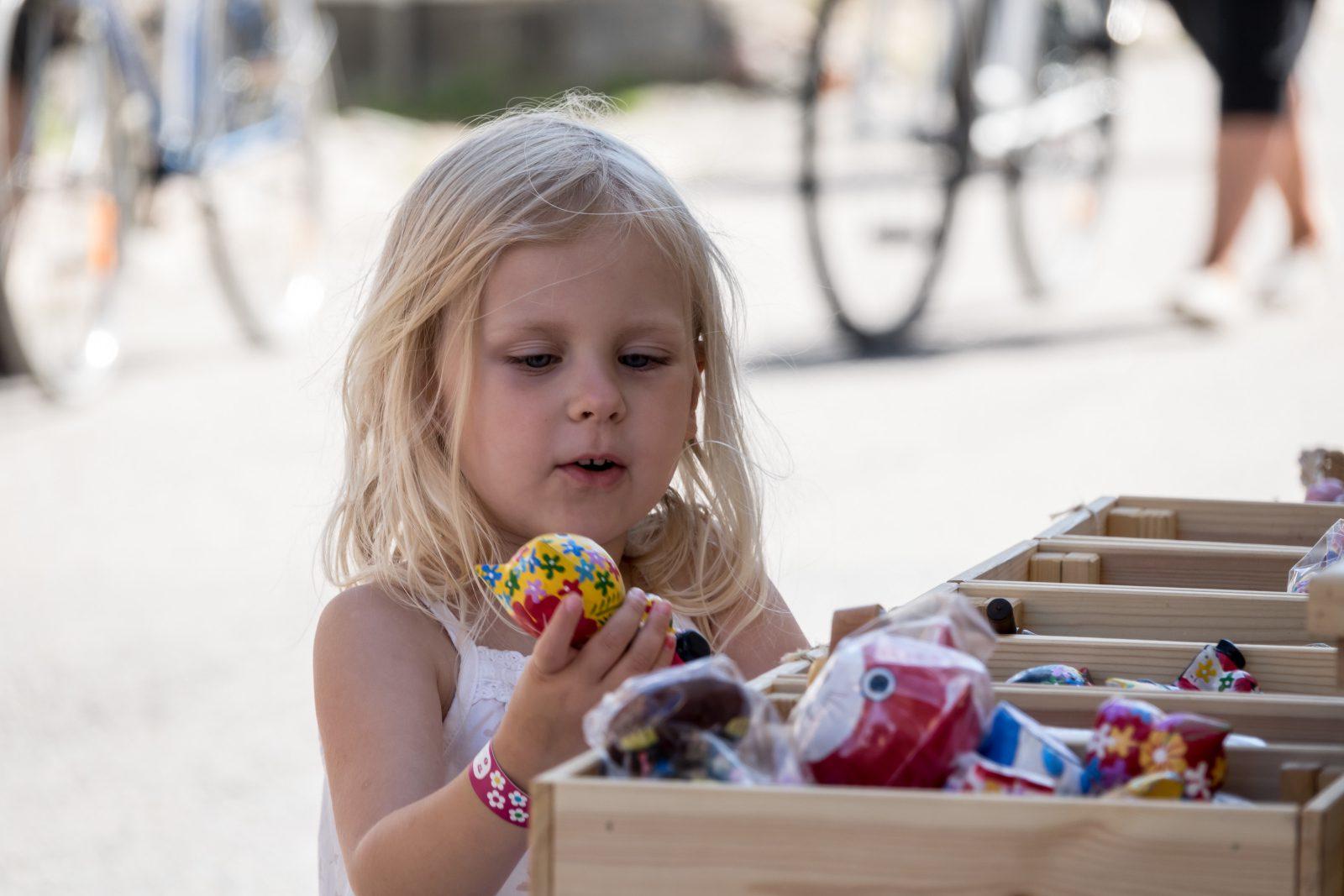 Vaaleahiuksinen tyttö pitää käsissään lelua, jonka on löytänyt myyntikojun laatikosta.