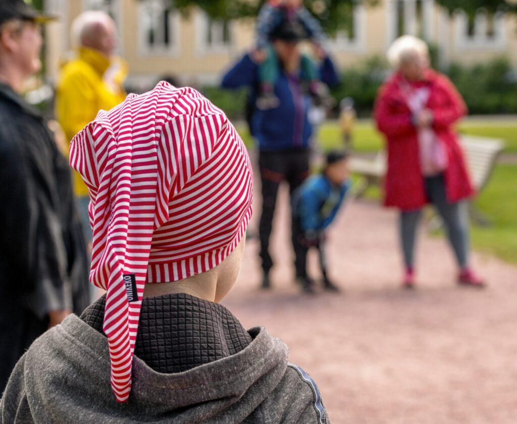 Harmaahupparinen lapsi, jolla päässä puna-valkoraidallinen myssy, jossa lukee Unikeko.