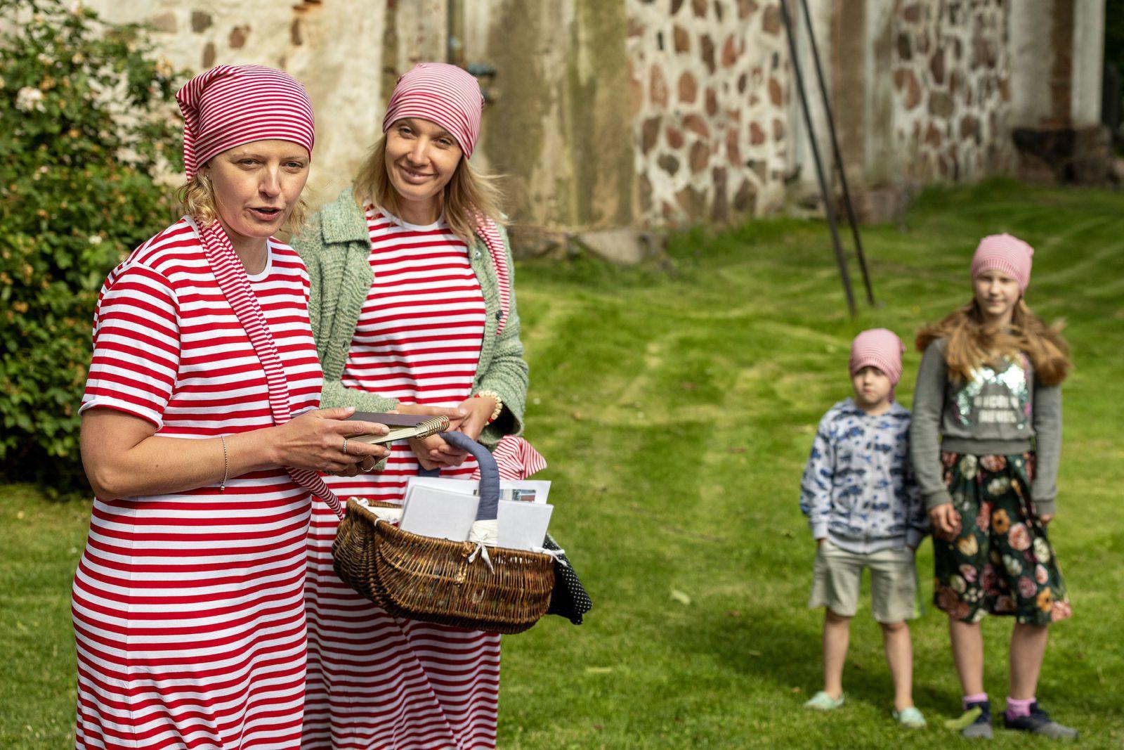 Kaksi punavalkoraidalliseen yöpukuun ja myssyyn pukeutunutta naisopasta opastaa lasten Unikeko -kierrosta Naantalin kirkon edustalla.