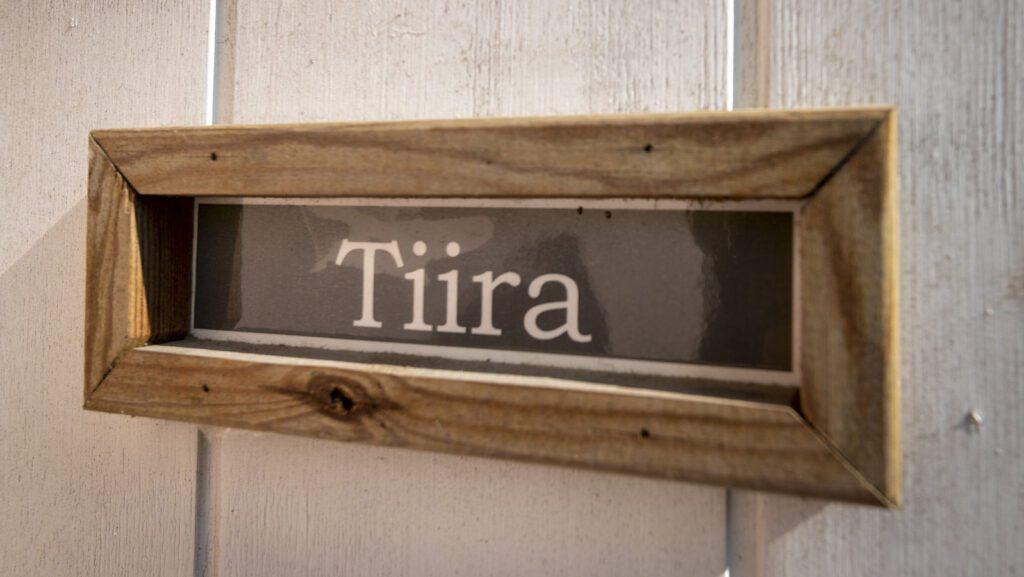 Puukehyksinen kyltti, jossa lukee Tiira.