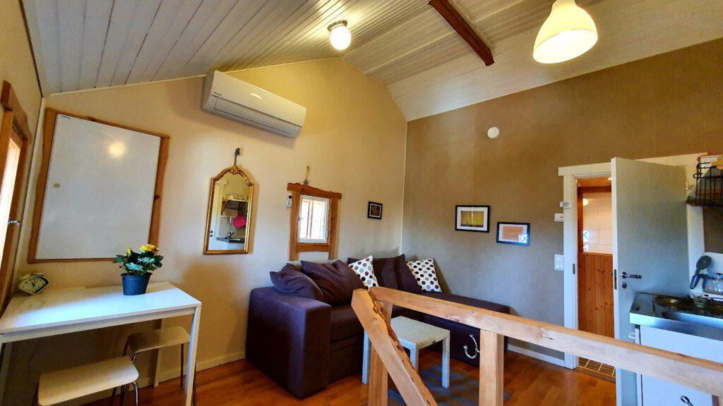Puutalohuoneiston olohuone, portaiden kaide ja ruskea sohva.