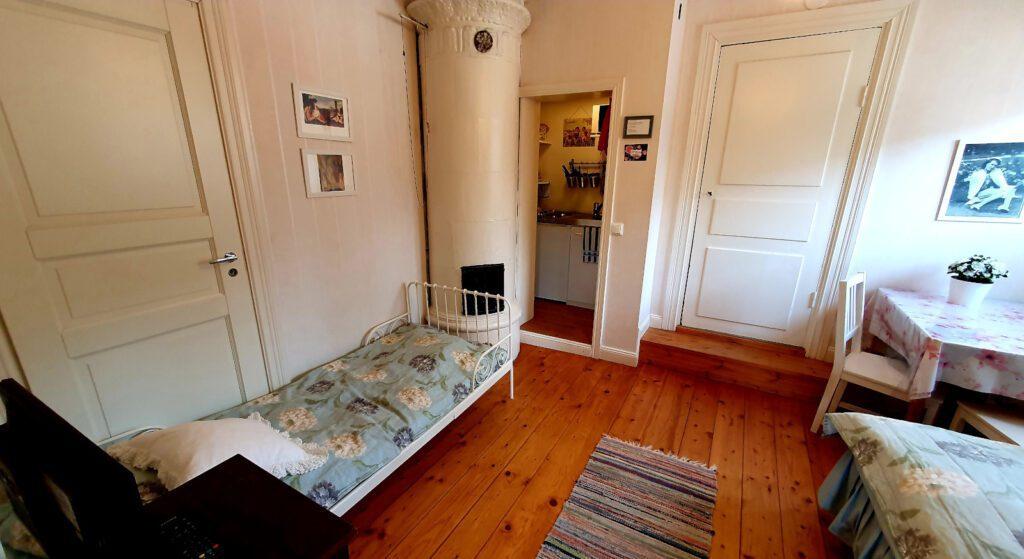 Puutalohuoneiston makuutila, parkettilattia, vuode, kakluuni ja keittiösoppi.