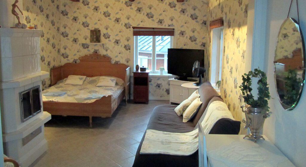Vanhan puutalohuoneiston makuuhuone, jossa puusänky, kaakeliuuni ja ruskea sohva.