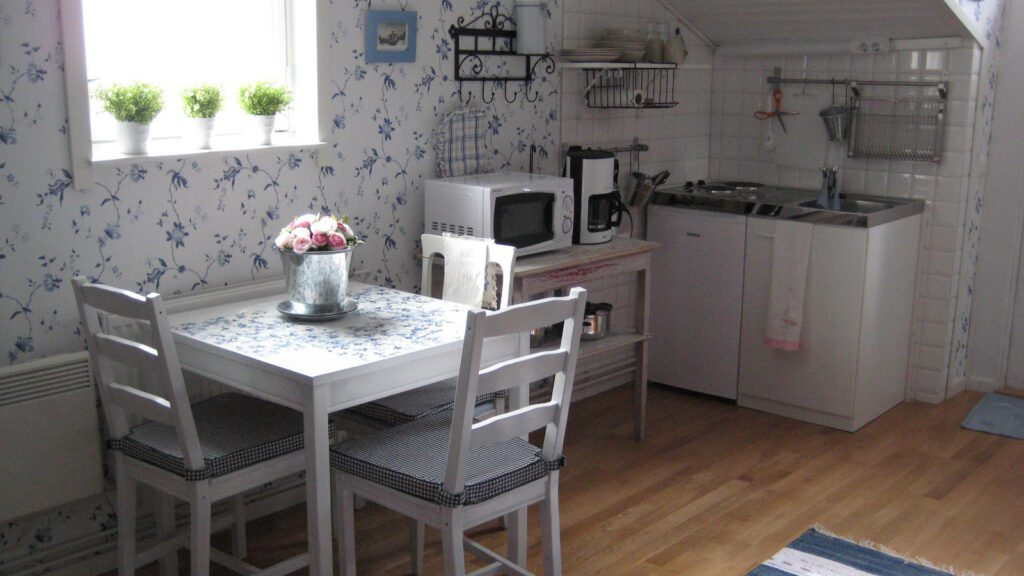 Puutalohuoneiston keittiönurkkaus, pöytä ja kolme tuolia, sinivalkokukkainen tapetti.