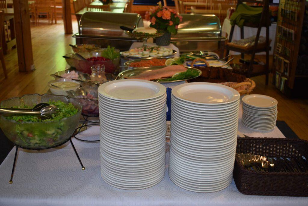 Buffetpöydän pää, kaksi korkeaa pinoa lautasia. Taustalla näkyy tarjoiluastioissa salaattia, lohta, rosollia, kananmunia ja leipää.