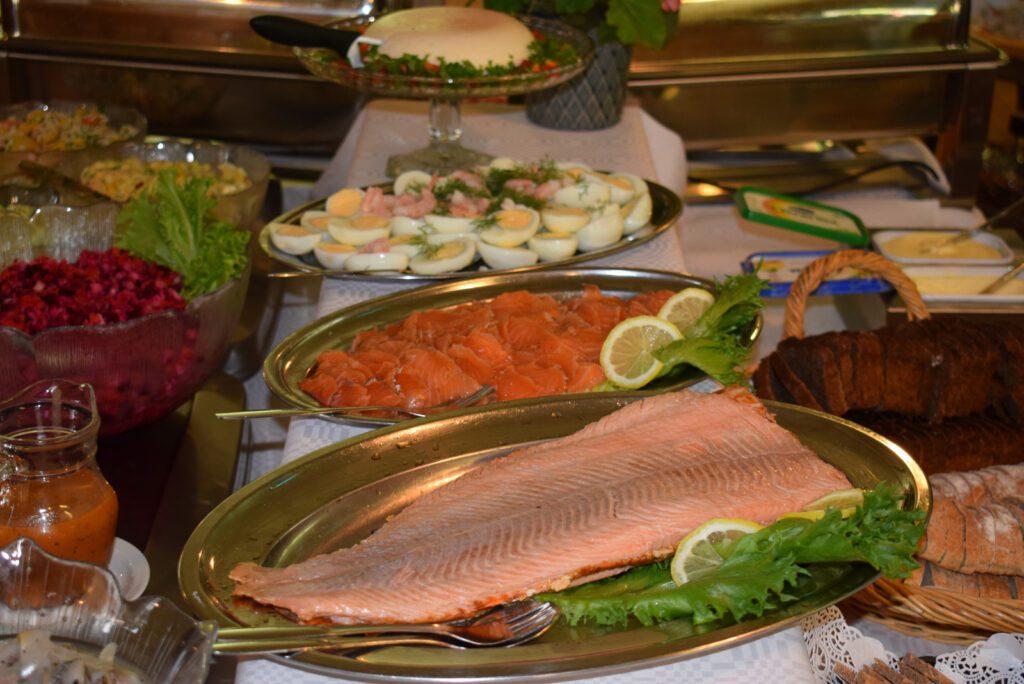 Buffetpöydän tarjoiluastioita, joissa lohta, rosollia, kananmunaa, leipää ja kotijuustoa.