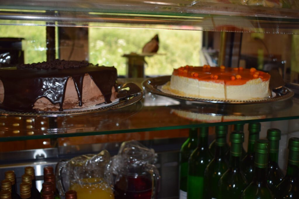 Vitriinissä suklaakakku ja oranssinvärinen tyrnijuustokakku.