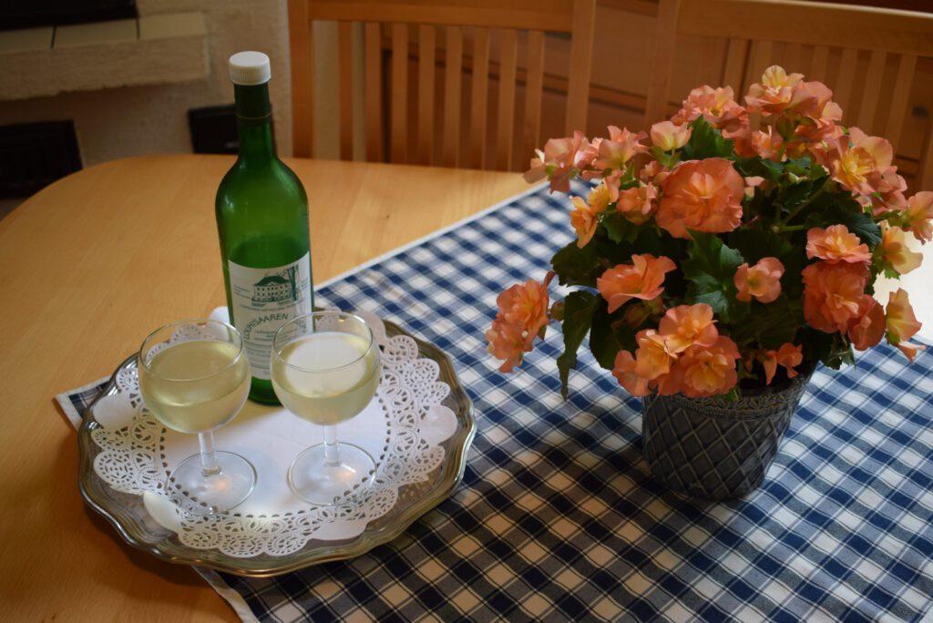 Pöydällä sinivalkoisen ruutuliinan päällä tarjottimella kaksi lasillista Louhisaaren juomaa ja vihreä pullo. Pöydällä ruukussa oransseja kukkia.
