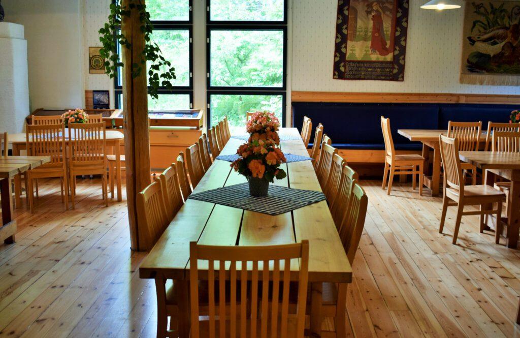 Louhisaaren kartanon kahvilan sali, keskellä pitkä puinen pöytä ja useita tuoleja. Pöydän päällä sinivalkoisia ruutuliinoja ja niiden päällä oransseja kukkia ruukuissa.