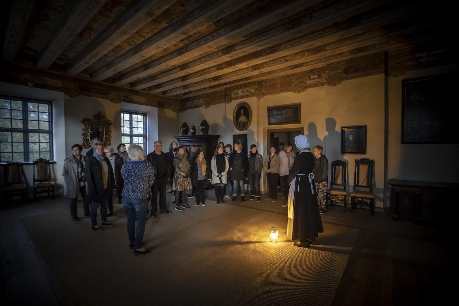 Louhisaaren kartanon hämärä juhlasali, ryhmä Louhisaaren kummituskierrokselle osallistuvia seisoo puoliympyrässä oppaan ja lattialla olevan lyhdyn ympärillä.