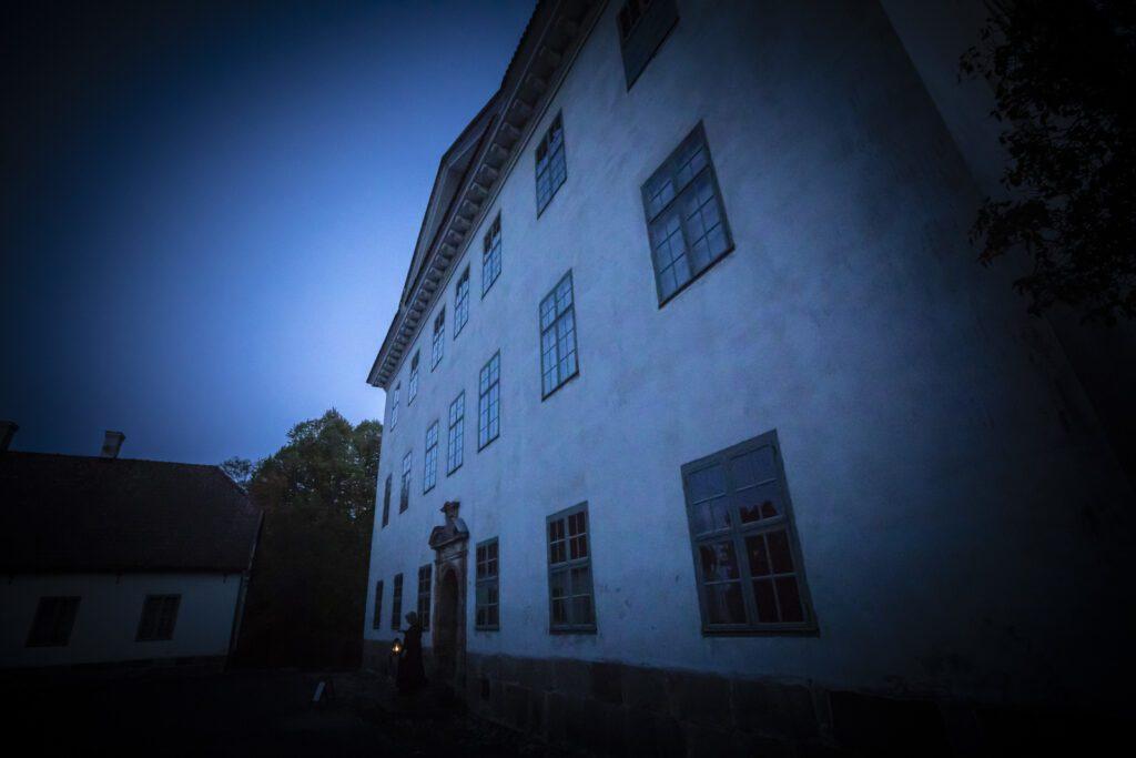 Louhisaaren kartanon valkoinen julkisivu hämärässä sinisessä valossa.
