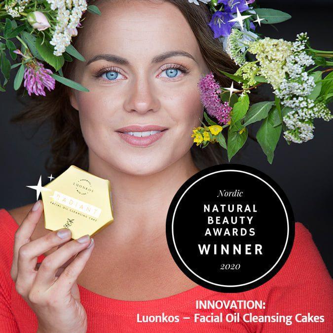 Luonkos luonnonkosmetiikan kuva naisesta, joka pitää kädessään puhdistuskakkua. Kuvassa logo jossa lukee Nordic natural beauty awards winner 2020.